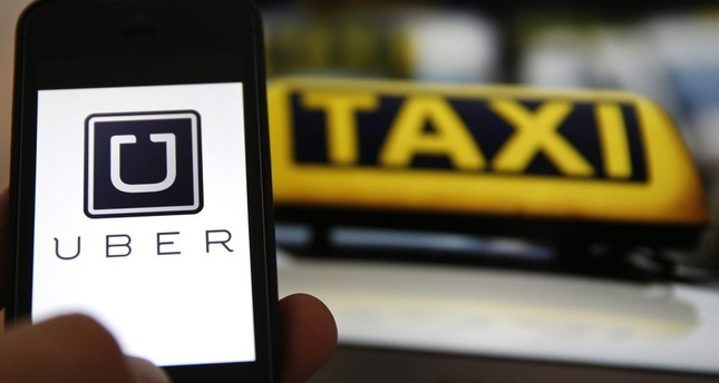 The logo of car-sharing service app Uber on a smartphone next to the picture of an official German taxi sign in Frankfurt, Sept. 15, 2014.