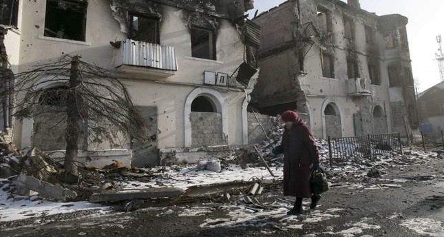 A woman walks past a damaged building in the town of Vuhlehirsk, Donetsk, Feb. 14, 2015. (REUTERS Photo)