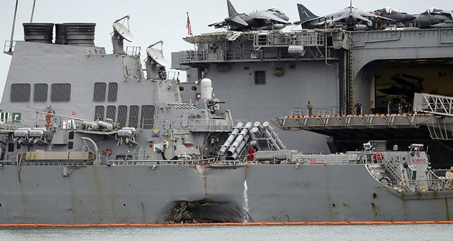 In this Aug. 22, 2017 file photo, the damaged port aft hull of USS John S. McCain, left, is seen while docked next to USS America at Singapore's Changi naval base in Singapore. (AP Photo)