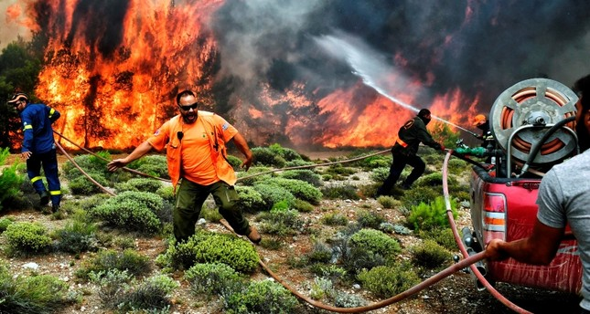 Firefighters and volunteers try to extinguish flames during a wildfire at the village of Kineta, near Athens, on July 24, 2018. (AFP Photo)