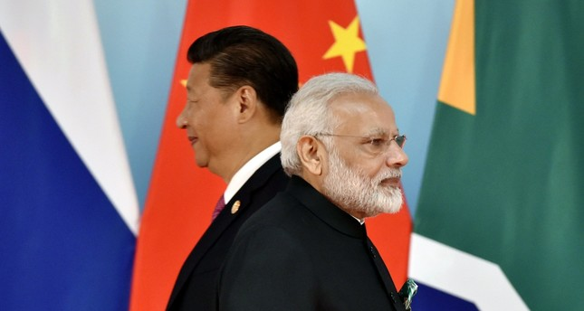 Chinese President Xi Jinping (L) and Indian Prime Minister Narendra Modi walk past each other as they attend a group photo session during the 2017 BRICS Summit in Xiamen, the Fujian province, China, Sept. 4.
