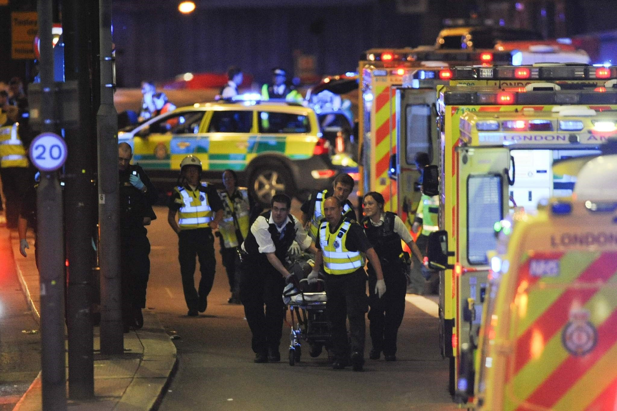 Police officers and members of the emergency services carrying a person injured in the terror attack on London Bridge on Saturday.