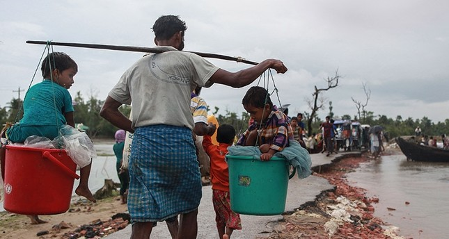 A Rohingya refugee carries two children in buckets as they arrive in Bangladesh at Shah Porir Dwip in Teknaf on September 9, 2017, as they flee violence in neighbouring Myanmar. (AFP Photo)