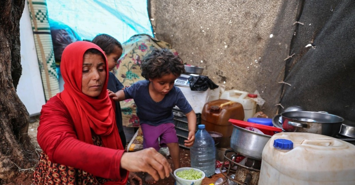 Mona Mutayr, a displaced Syrian mother, prepares an iftar meal in a field near a camp for displaced people in the village of Atme, near the Turkish border, May 23, 2019.