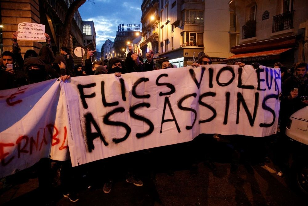 Demonstrators hold a banner reading ,Cops, rapers, killers, during a protest against alleged police abuses, in Paris, Feb. 15.