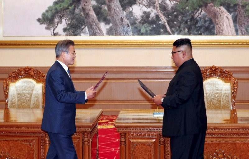 South Korean President Moon Jae-in, left, and North Korean leader Kim Jong Un approach to exchange the documents after signing at the Paekhwawon State Guesthouse in Pyongyang, North Korea, Sept. 19, 2018. (Pyongyang Press Corps Pool via AP)