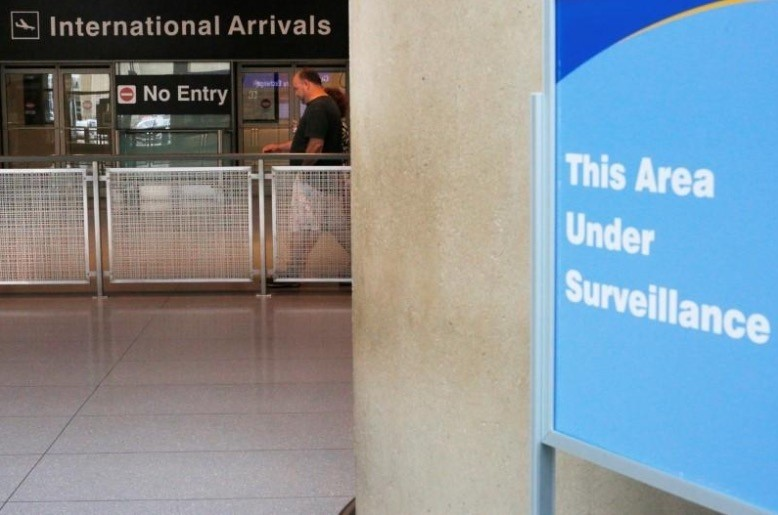 A sign warns of surveillance at the International Arrival area at Logan Airport in Boston. (Reuters Photo)