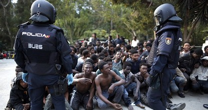 pAlmost 500 migrants forced their way into Spanish territory in North Africa early Friday by breaking through gates in the 20-foot (6-meter) high fence that separates Morocco from Spain's Ceuta...