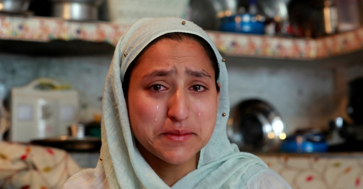 A woman weeps after her household goods were damaged by Indian security forces following clashes between protesters and the security forces on Friday, during restrictions after the scrapping of the special status for Kashmir (Reuters Photo)