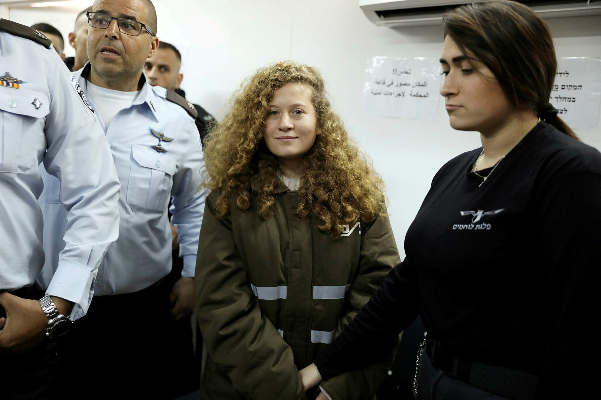 Palestinian Ahed Tamimi, 17, enters a military courtroom escorted by Israeli security personnel at Ofer Prison near the West Bank city of Ramallah, Jan. 15.