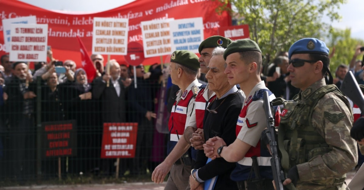 Gendarme troops accompany Aku0131n u00d6ztu00fcrk to the first hearing of the trial in Ankara, as families of coup victims protest him, May 22, 2017.