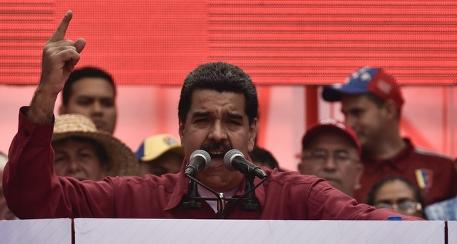 Venezuela's President Nicolas Maduro stands next to a sign that reads Trump go away from Latin America gives a speech at a rally against Trump in Caracas, August 14, 2017. AA Photo