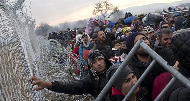 Migrants and refugees wait along the wire fence that separates the Greek side from the Macedonian one, in their effort to  cross into Macedonia at the northern Greek border station of Idomeni, Friday, Dec. 4, 2015 (AP Photo)