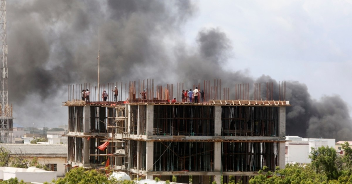 Workers are seen on a construction site as smoke billows from the scene of an explosion in Mogadishu, Somalia July 22, 2019. (Reuters Photo)