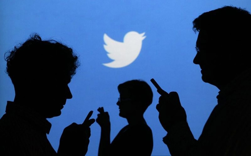 People holding mobile phones are silhouetted against a backdrop projected with the Twitter logo in this illustration picture taken in Warsaw in this September 27, 2013 file photo. (Reuters Photo)