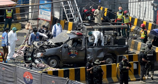 Pakistani security personnel surround a damaged police van in Lahore, Pakistan, Wednesday, May 8, 2019. (Reuters Photo)