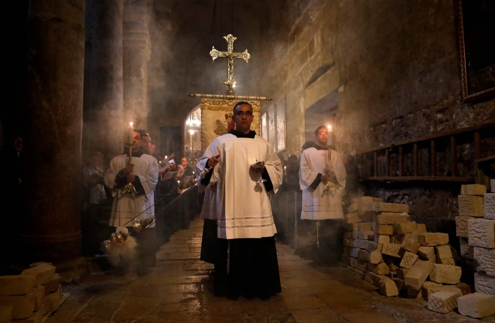 Franciscan friars pray during the Lenten procession inside the Church of the Holy Sepulchre in the Old City of Jerusalem.