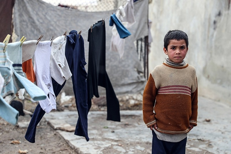 Displaced Syrian boy stands in his shelter in al-Asha'ari, Eastern al-Ghouta, Syria, 18 January 2018. (EPA Photo)