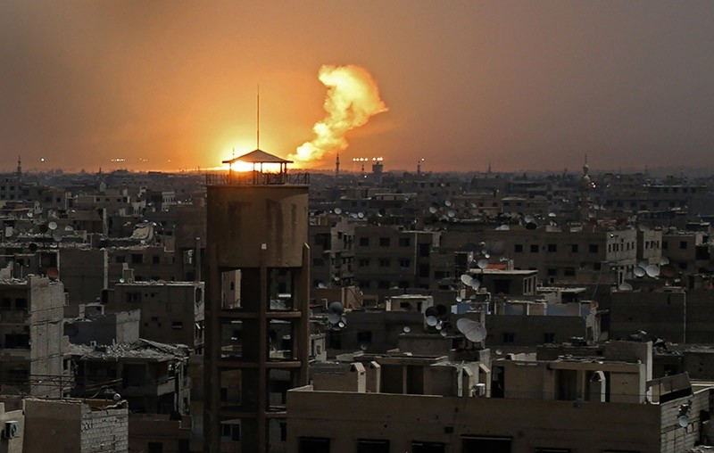 A picture taken on February 28, 2018 shows flames erupting in the horizon following a reported rocket attack in the rebel-held enclave of eastern Ghouta on the outskirts of the Syrian capital Damascus. (AFP Photo)