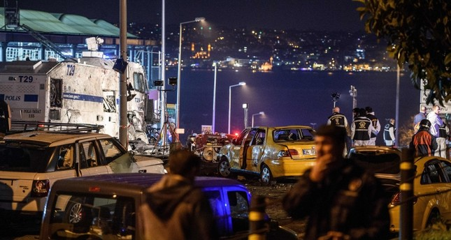 Turkish police officers and forensic work next to damaged police vehicles and cars on the site where a car bomb exploded near the stadium of football club Beşiktaş in central Istanbul on December 10, 2016. (AFP Photo)