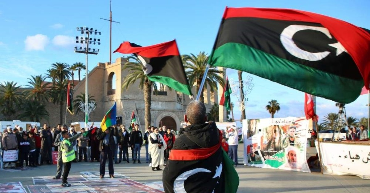 A protester waves Libyan flags at a rally to protest attacks by forces linked to putschist Gen. Khalifa Haftar in Tripoli, on Jan. 17, 2020. (AA Photo)
