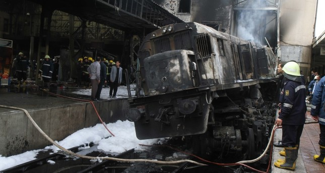 Fire fighters and onlookers gather at the scene of a fiery train crash at the Egyptian capital Cairo's main railway station on February 27, 2019. AFP Photo