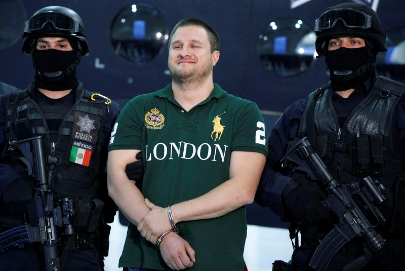 In this Aug. 31, 2010 file photo, Texas-born fugitive Edgar Valdez Villarreal, also known as ,La Barbie,, center, reacts during his presentation to the media after his arrest in Mexico City. (AP Photo)