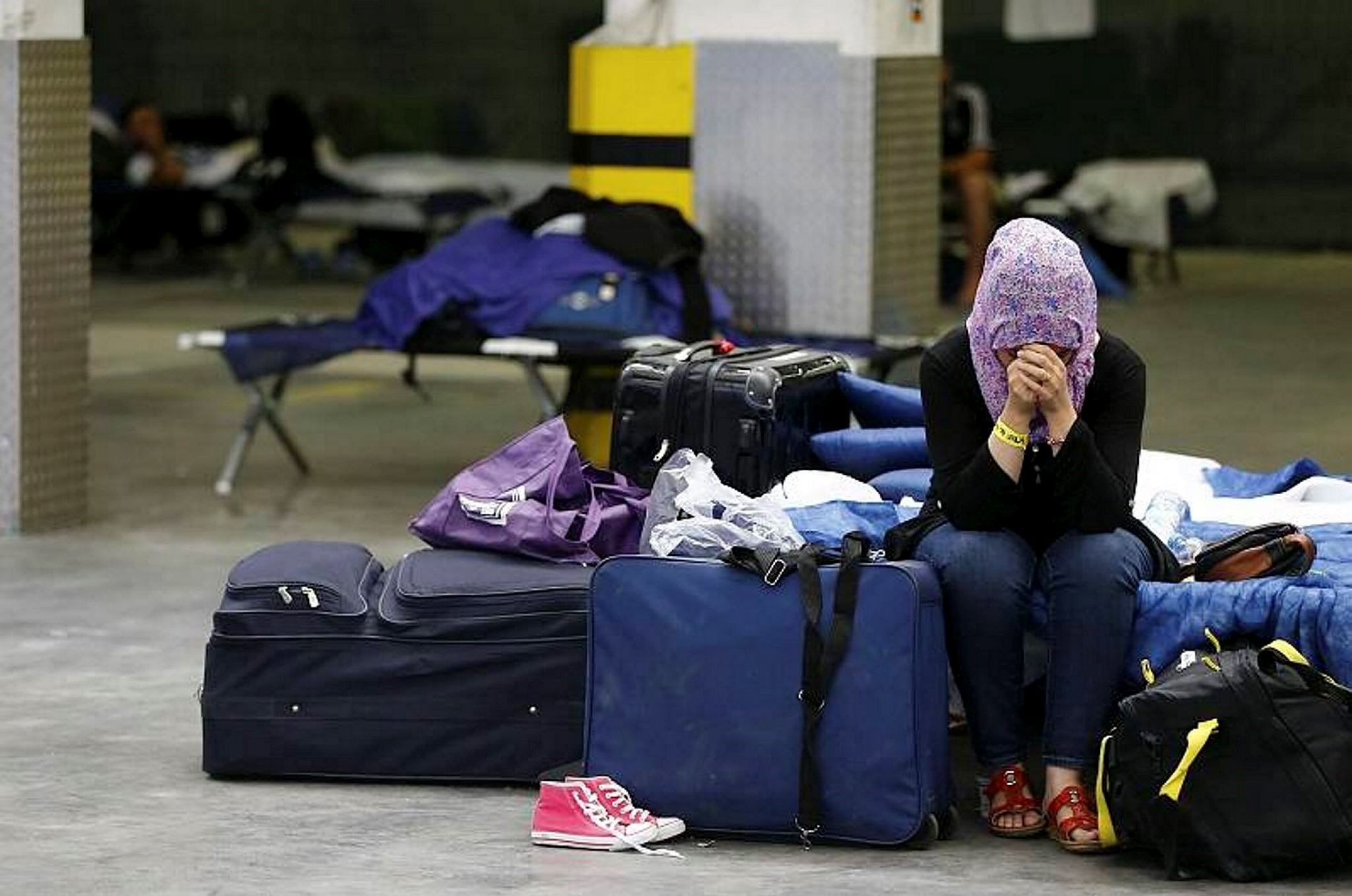 A Syrian woman cries as she sits on a folding bed in a former newspaper printing house used as a refugee registration centre for the German state of Hesse in Neu-Isenburg, September 11, 2015. (FILE Photo)