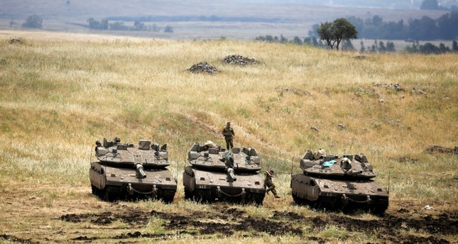 An Israeli soldier stands on a tank as another jumps off it near the Israeli side of the border with Syria in the Israeli-occupied Golan Heights, Israel, May 9, 2018. (REUTERS Photo)