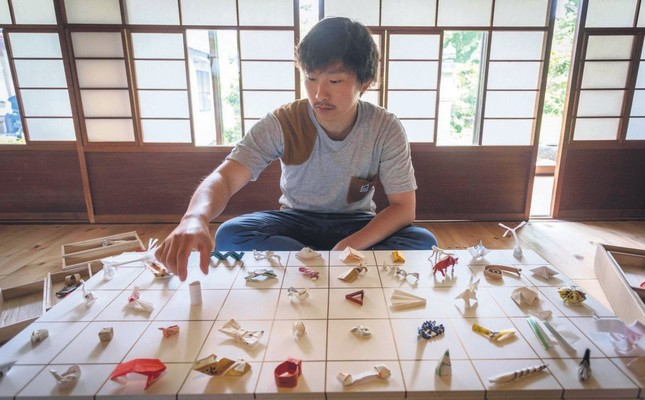 Yuki Tatsumi sits next to his collection of origami made from chopstick sleeves.