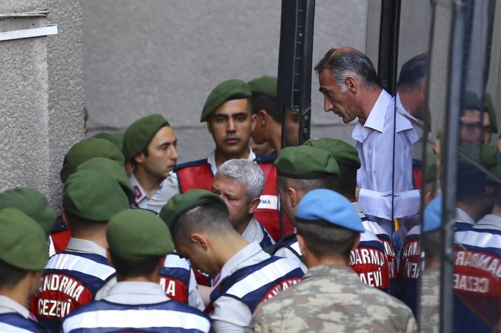 Gendarmerie troops escort the defendants to the courtroom.