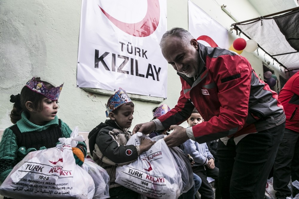 Turkish Red Crescent President Dr. Kerem Ku0131nu0131k delivers toys, clothes and stationery to children in Idlib, Syria.