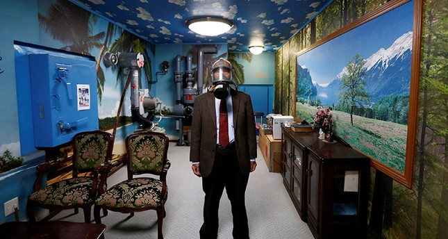 Seiichiro Nishimoto, CEO of Shelter Co., poses wearing a gas mask at a model room for the company's nuclear shelters in the basement of his house in Osaka, Japan April 26, 2017. (Reuters Photo)