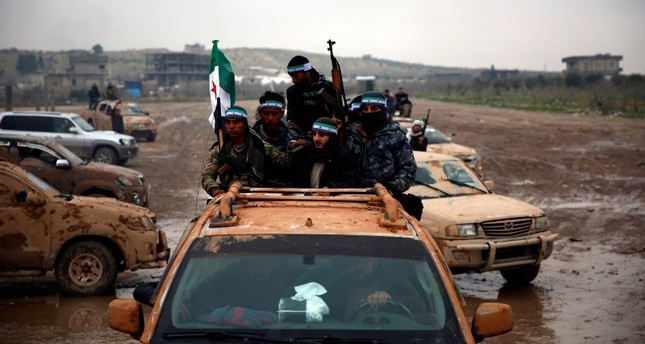 This Dec. 25, 2018 photo shows the Free Syrian Army (FSA) fighters in the back of their trucks as they leave their barracks in the town of Jarabulus, as they prepare to move towards Manbij. (AFP Photo)