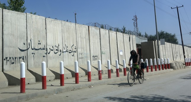 An Afghan man pedals his bicycle past American University of Afghanistan in Kabul, Afghanistan, Monday, Aug. 8, 2016. AP Photo