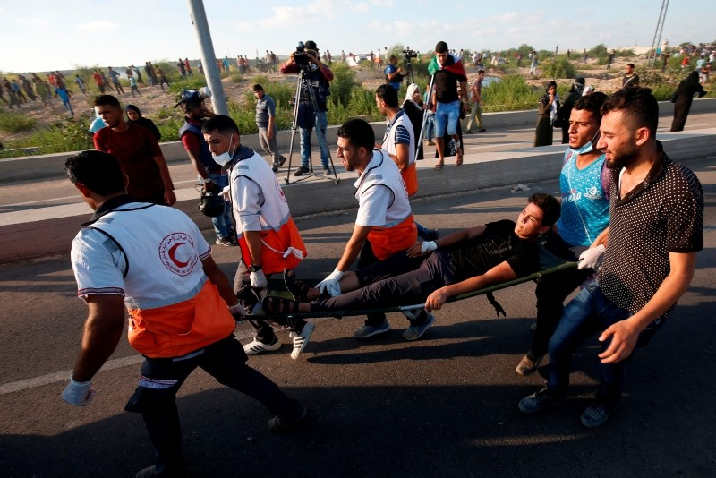 Medics help evacuate a wounded Palestinian protestor during a demonstration at the Erez crossing with Israel on September 18, 2018, in the northern Gaza Strip. (AFP Photo)