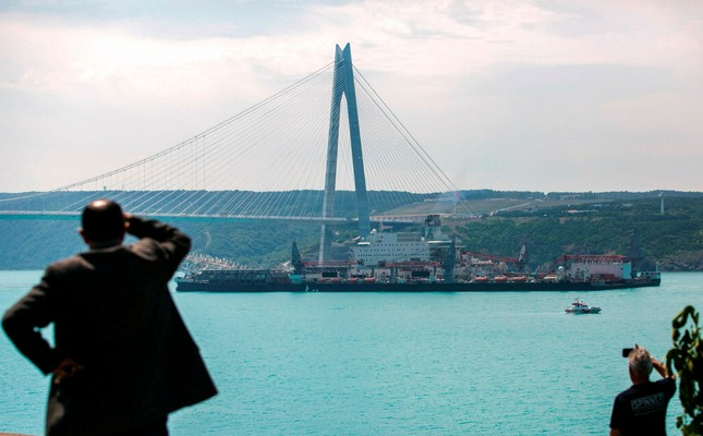 People look at the the Pioneering Spirit vessel, which will carry out construction of the offshore section of the Turkish Stream natural gas pipeline, passing the Yavuz Sultan Selim bridge on the Bosphorus on May 31,2017 in Istanbul (AFP Photo)