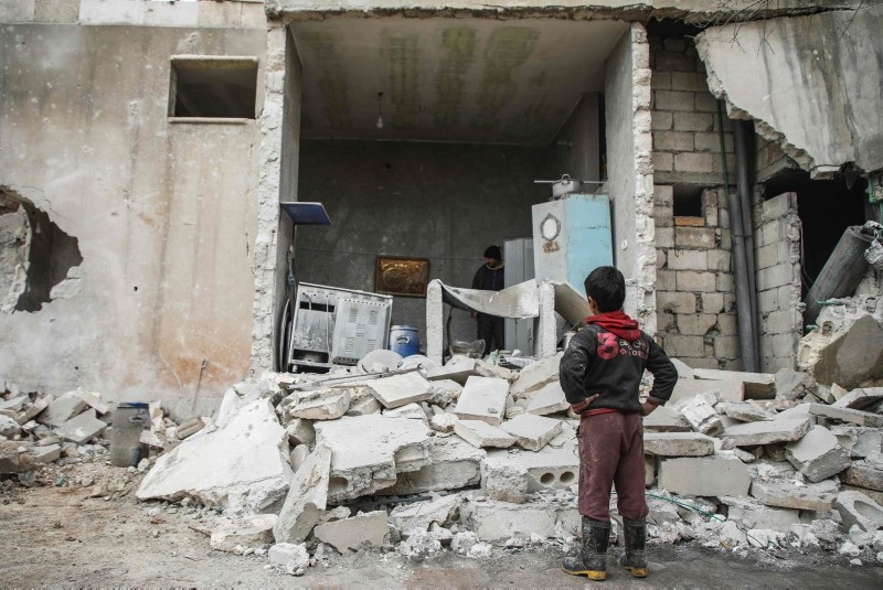 A Syrian boy looks at the fallen wall of a house which was damaged by an airstrike. (AFP Photo)