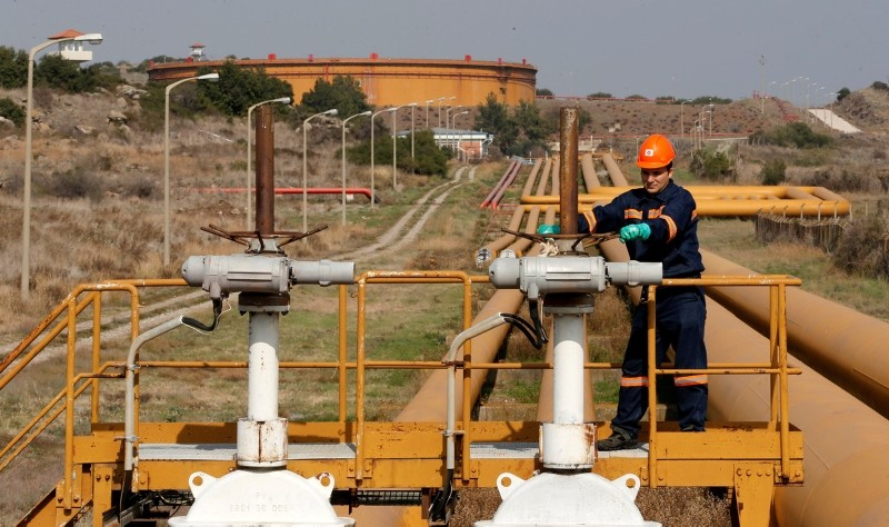A worker checks the valve gears of pipes linked to oil tanks at Turkey's Mediterranean port of Ceyhan, which is run by state-owned Petroleum Pipeline Corporation (BOTAu015e), some 70 kilometers (43.5 miles) from Adana, February 19, 2014. (Reuters Photo)