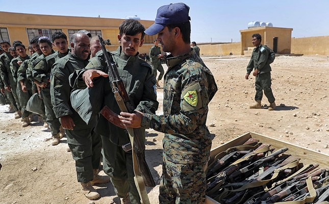 The so-called Syrian Internal Security Forces, with visible insignia of PKK offshoot YPG group, receive weapons during their graduation ceremony, at Ain Issa desert base, in Raqqa province, northeast Syria, Thursday, July 20, 2017. (AP Photo)