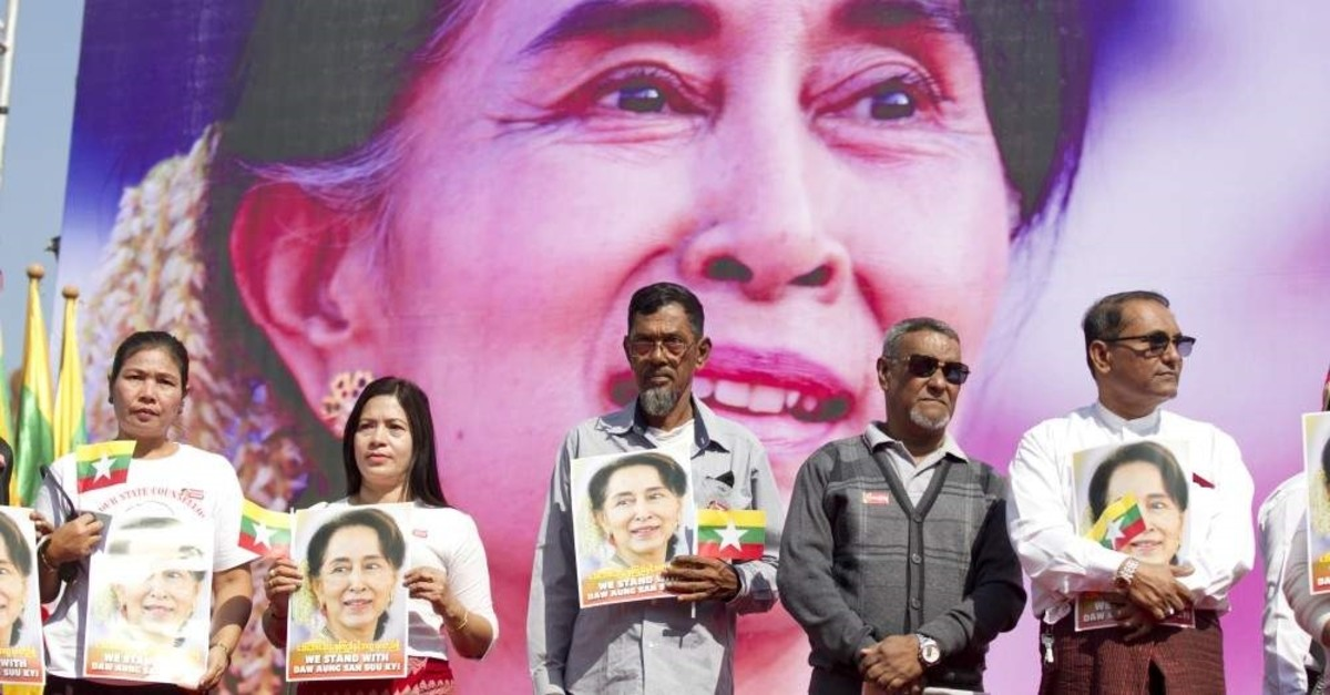 In this Tuesday, Dec. 10, 2019 file photo, Members of Myanmar Muslims community hold portraits of Myanmar leader Aung San Suu Kyi to pray as they gather in front of City Hall in Yangon, Myanmar. (AP Photo)