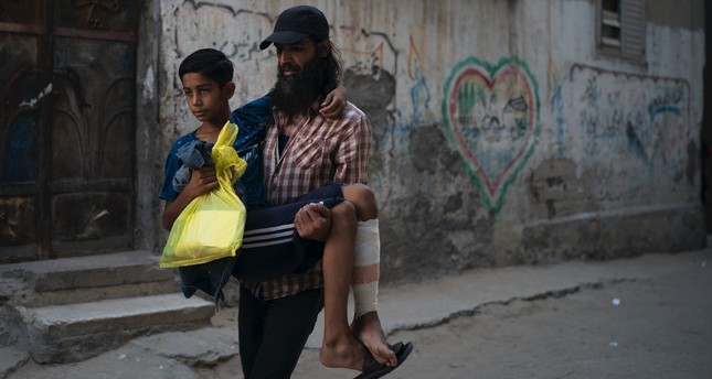 A Palestinian carries his 12-year-old son who was shot in the leg at one of the demonstrations on the  Gaza strip's border with Israel, Sept. 16.