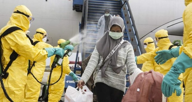 A handout photo made available by the Indonesian Foreign Ministry shows Indonesian nationals, who were evacuated from Wuhan, China, being sprayed with antiseptic as they arrive at Hang Nadim Airport in Batam, Indonesia, Feb. 2, 2020. EPA/Indonesian Foreign Ministry/Handout