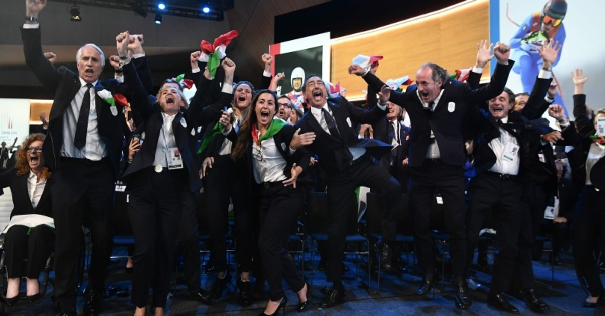 Members of the delegation of Milan/Cortina d'Ampezzo 2026 Winter Olympics candidate city react after the city was elected to host the 2026 Olympic Winter Games during the 134th session of the IOC, in Lausanne. (AFP Photo)