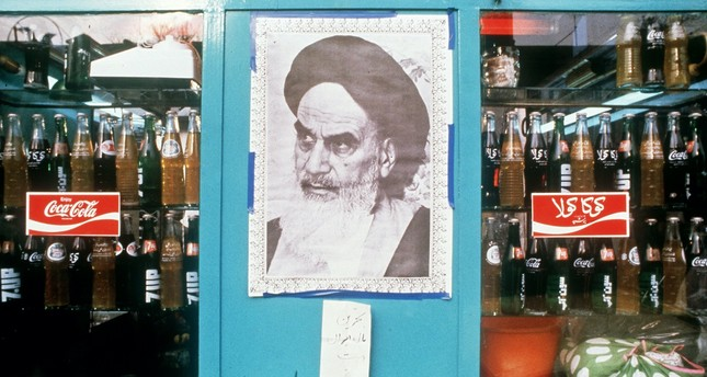 A poster of Iranian leader Ayatollah Khomeini in a shop window next to bottles of Coca-Cola, Tehran, Jan. 1, 1979.