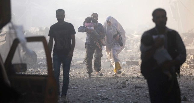 Syrians emerge from a dust cloud following an airstrike on Kafr Batna, in the moderate-held Eastern Ghouta area, on the outskirts of the capital Damascus, Syira, Sept. 30, 2016.
