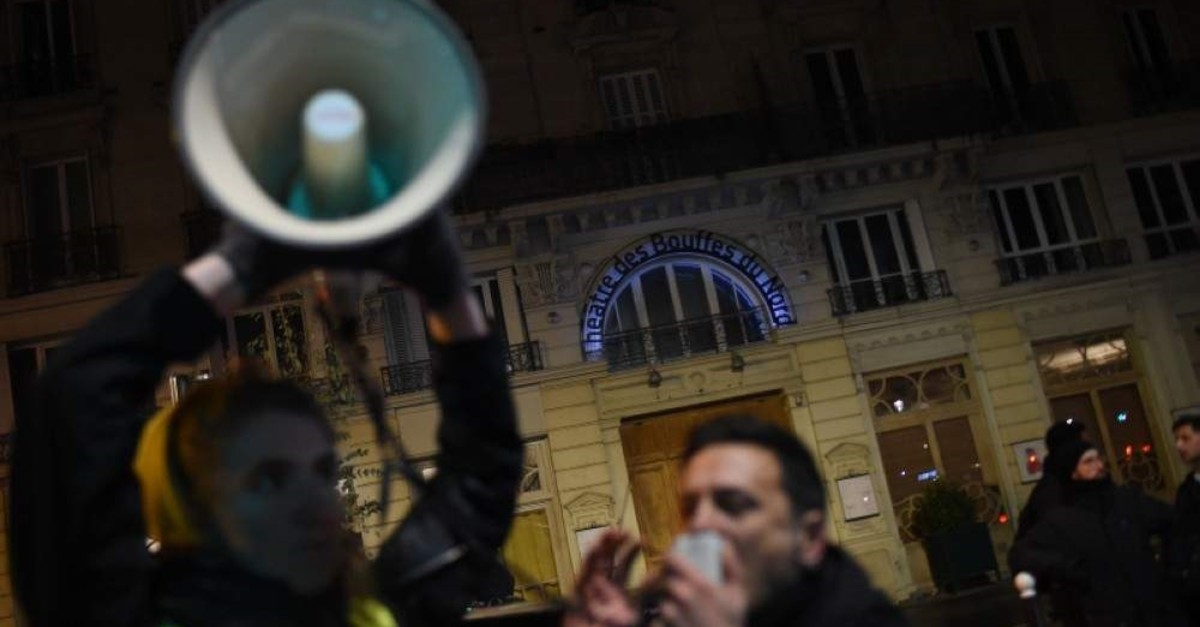 A protestor speaks into a megaphone during a demonstration in front of the Bouffes du Nord theater in Paris as French President Emmanuel Macron attends a play, Jan. 17, 2020. (AFP Photo)