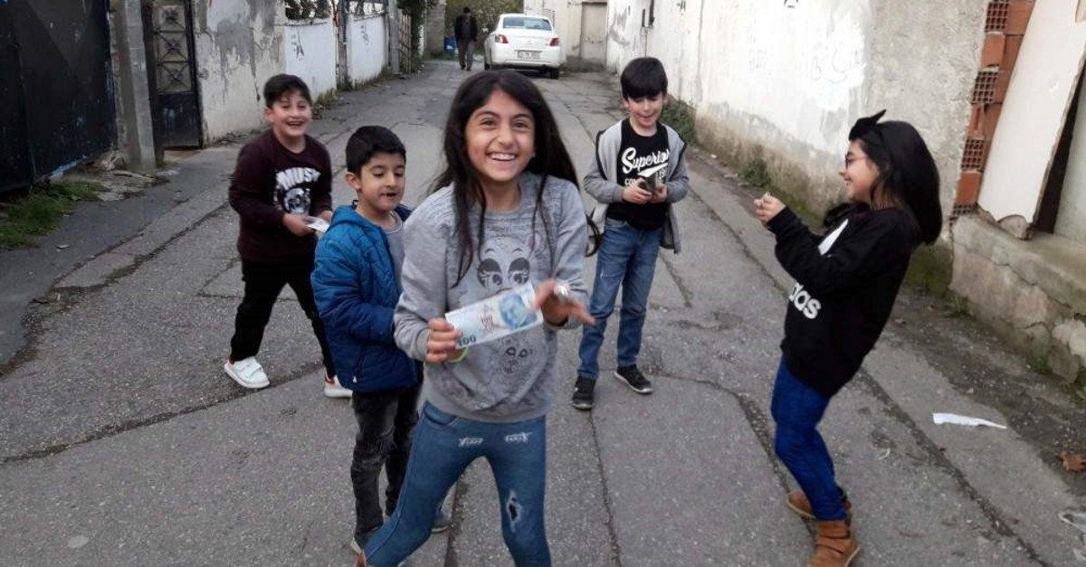 Children in a neighbourhood in Istanbul's Atau015fehir pose after a mysterious philanthropist appeared on the streets and gave them pocket money. (DHA Photo)