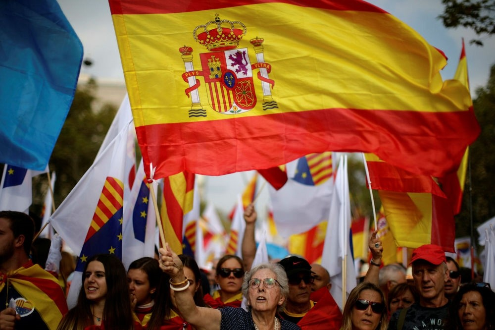 A woman waves a Spanish flag while celebrating the country's national day in Barcelona, Oct. 12.