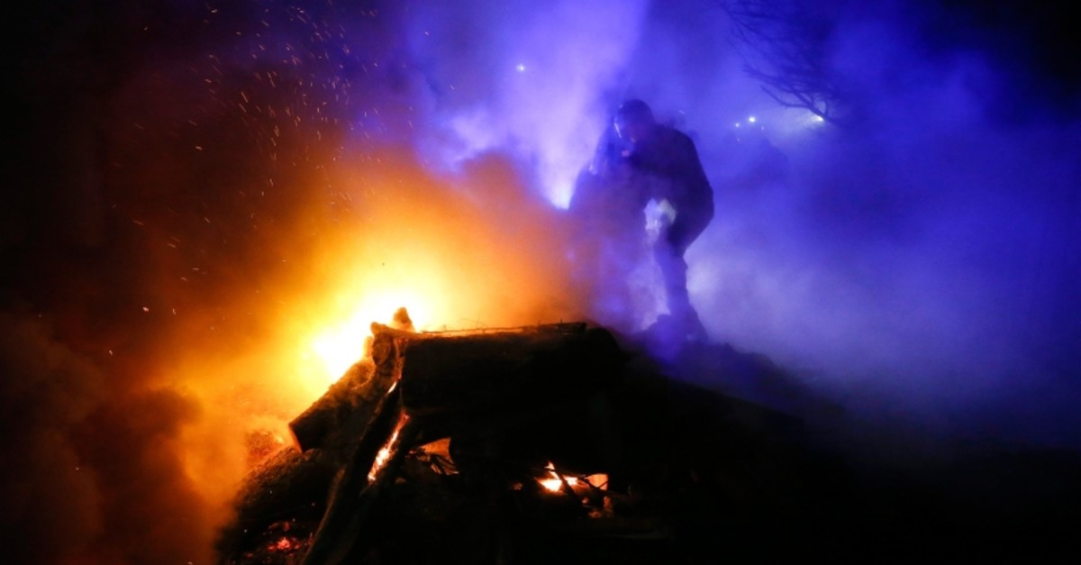 A protester, who planned to stop buses carrying passengers evacuated from the Chinese city of Wuhan, kindles a fire outside Novi Sarzhany, Ukraine, Thursday, Feb. 20, 2020. (AP Photo)